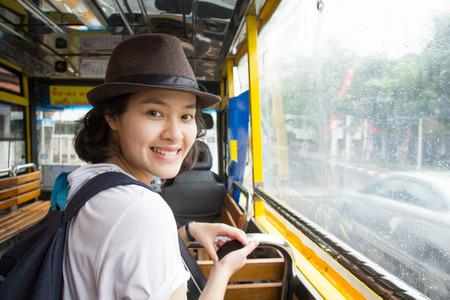 viagem: Mulher asiática nova no ônibus com dia chuvoso.