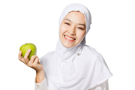 green smiley face: beautiful young Muslim woman holding green apple with smiley face isolated on white background.
