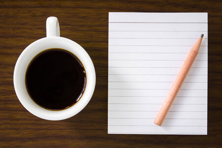 Coffee cup with note book and pencil on table background. photo
