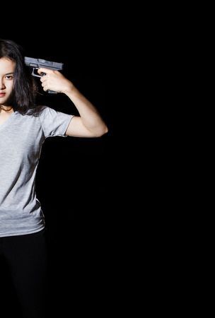 Woman aiming a gun on her head isolated on black background. photo