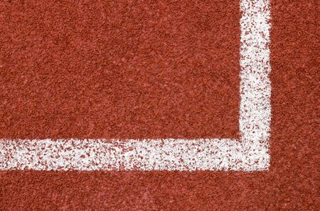 redbrick: Corner of running track with white striped on redbrick color background. Stock Photo