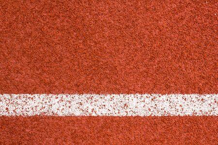 redbrick: Running track with white striped on redbrick color background.
