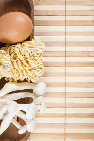 Egg, noodles and mushroom on bamboo mat background. photo