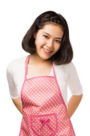 Jonge Aziatische vrouw, gekleed in roze keukenschort op een witte achtergrond.