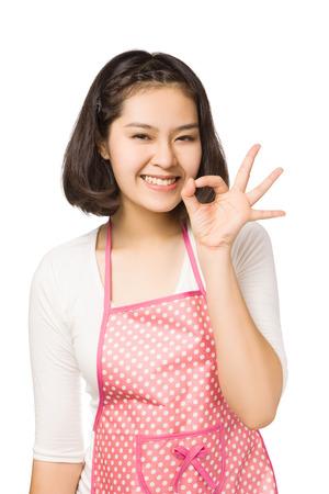 Mooie jonge Aziatische vrouw, gekleed keukenschort en het tonen van ok, geïsoleerd op een witte achtergrond.