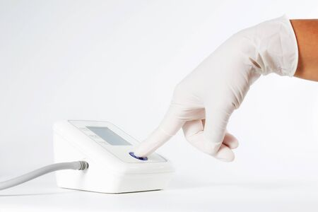 systolic: Female hands wear glove press start button on blood-pressure meter isolated on white background. Stock Photo