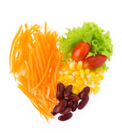 food concept: Delicious salad put in heart shape isolated on white background. Stock Photo