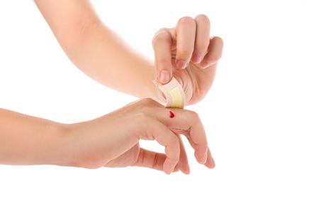 hemorragias: Dé poner una tirita en el dedo herido aislado en el fondo blanco. Foto de archivo