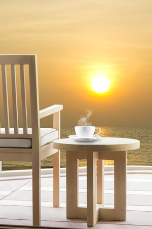 Wooden relax chairs and coffee cup with sunrise on the sea  view background.