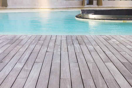pool deck: Wooden platform beside blue swimming pool background. Stock Photo