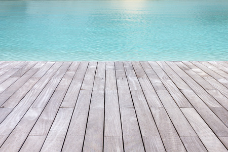 from side: Wooden platform beside blue swimming pool background. Stock Photo