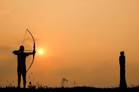 tight focus: Silhouette archery shoots a bow at a target in sunset sky and cloud.