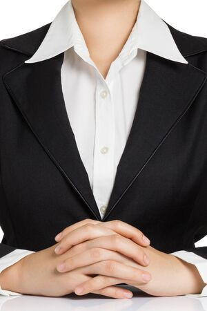 clasped hand: Business woman body in black suit with hand clasped on table.