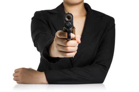 pistols: Business woman in a black suit aiming a gun at the camera isolated on white background.