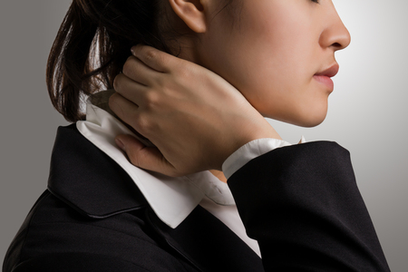 Close up young businesswoman in black suit holding hand on the pained neck.
