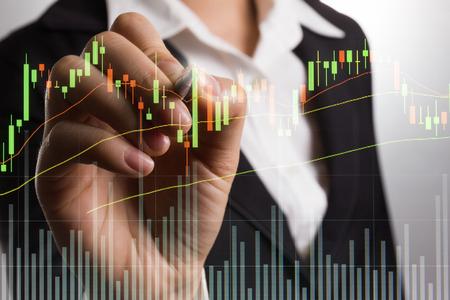 comercio: Empresario escrito analizar el gráfico para el mercado de venta de acciones en la pantalla. Foto de archivo