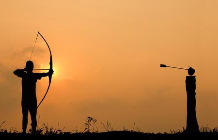 Silhouet boogschieten schiet een boog op een appel op hout in zonsondergang hemel en cloud. Stockfoto