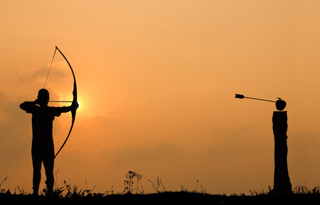 tight focus: Silhouette archery shoots a bow at an apple on timber in sunset sky and cloud. Stock Photo