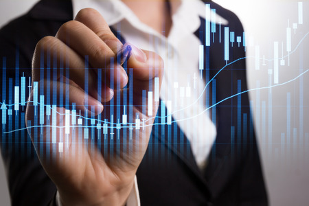 stock: Businessman writing analyze graph for trade stock market on the screen. Stock Photo