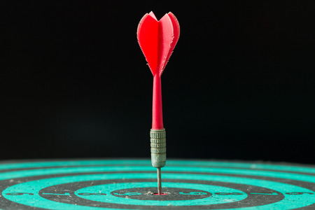 dart on target: Red dart arrow hitting in the center of green dartboard. Stock Photo