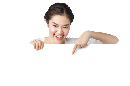 woman holding sign: Young smiley Asian woman showing and pointing at blank billboard sign banner isolated on white background. Stock Photo