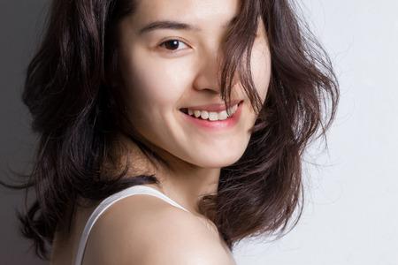 웃는 얼굴로 젊은 아시아 여자를 닫습니다.