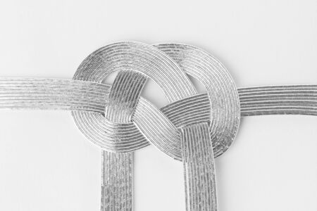 lazo regalo: decorative Japanese cord made from silver ribbon on white paper background.