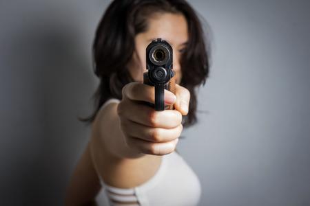 pistolas: Mujer que apunta un arma de fuego; foco en el arma.