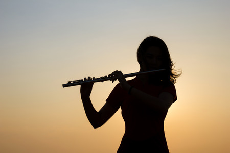 Silhouette woman playing flute in sunset sky background.