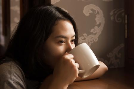 mujer tomando cafe: La mujer asiática goza de café recién hecho en la mañana cerca de la ventana. Foto de archivo