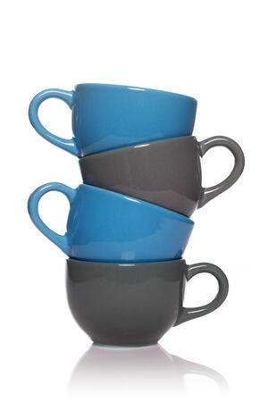 ceramiki: Stos niebieski i szary filiżanek herbaty na białym tle.