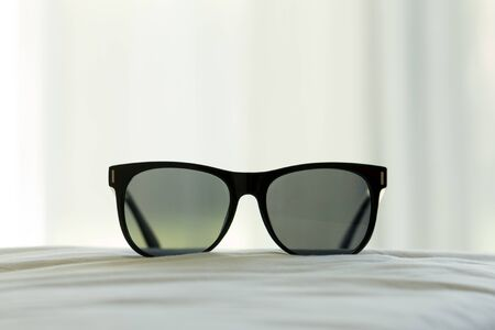 selective focus: Black sun glasses in the bed room with soft focus.