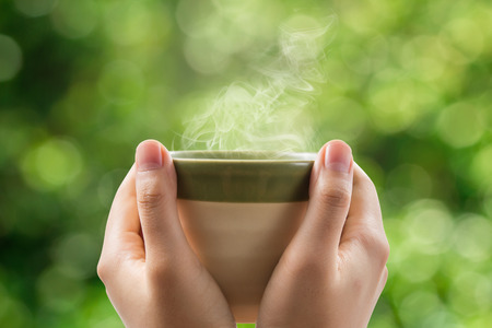 Hands holding tea cup on green bokeh background.