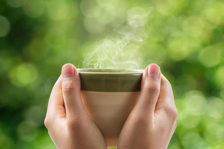 tazza di te: Mani che tengono tazza di tè su sfondo verde bokeh. Archivio Fotografico