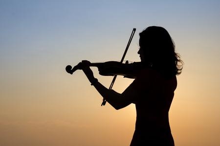 일출 하늘 배경에 바이올린을 연주 여자의 실루엣입니다.
