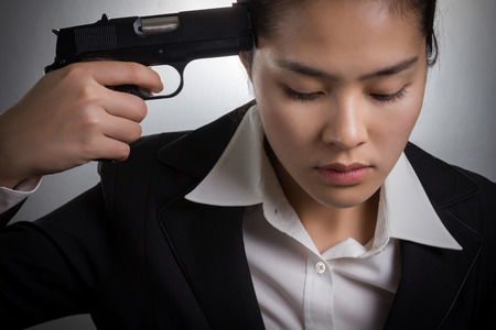 holding gun to head: Young Asian businesswoman in depression while hand holding gun aiming to her head. Stock Photo