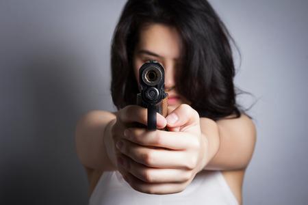 mujer con arma: Mujer que apunta un arma de fuego, se centran en la pistola. Foto de archivo