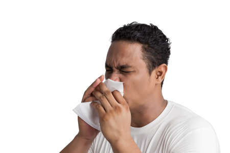 flu vaccination: Closeup portrait of young man in white t shirt with allergy or cold, blowing his nose with a tissue, Flu season and vaccination.