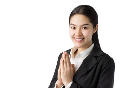 Bedrijfsvrouw in zwarte kostuumgroet met Thaise cultuur Sawasdee, welkom die uitdrukking op witte achtergrond wordt geïsoleerd. Stockfoto