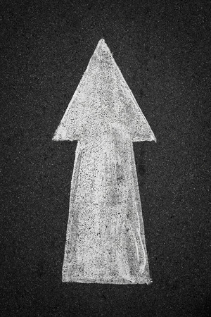 paved: White arrow sign go forward direction on paved road. Stock Photo