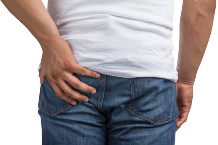 back ache: Young man with hand touching his bottom isolated on white background. Stock Photo