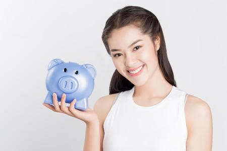 ganancias: feliz mujer asiática joven que sostiene hucha azul. Foto de archivo