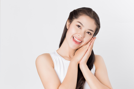 Young Asian woman looking upward with smiley happy face, day dreaming.