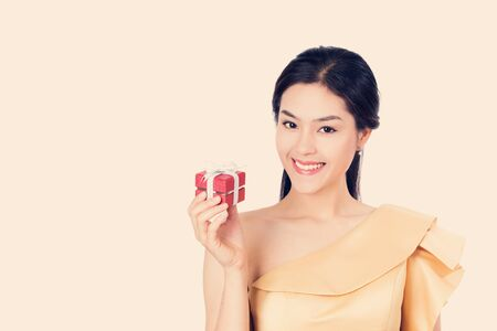 celebration smiley: Beautiful happy smiley Asian women holding red gift box, present. Stock Photo