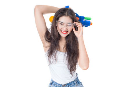 Young happy beauty Asian woman holding plastic water gun at Songkran festival, Thailand. Isolated on white background. Фото со стока - 75935226