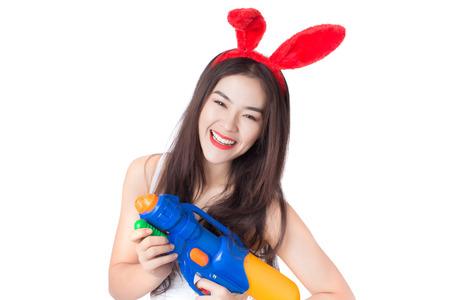 lapin sexy: Jeune heureux beauté femme asiatique tenant un pistolet à eau en plastique au festival de Songkran, en Thaïlande. Isolé sur fond blanc. Banque d'images