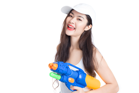 celebration smiley: Young happy beauty Asian woman holding plastic water gun at Songkran festival, Thailand. Isolated on white background.