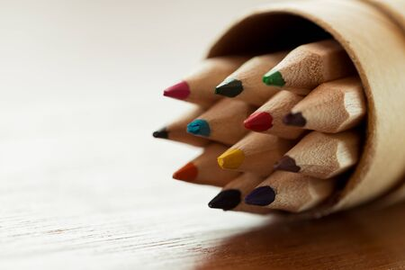 Close up multi wooden color pencil in a container on the table in the classroom. Stock Photo