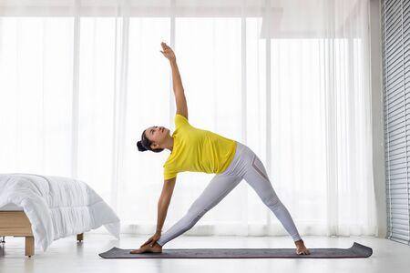 junge asiatische Dame mit gelbem T-Shirt, die morgens nach dem Aufwachen Übung Yoga-Pose im Schlafzimmer macht.