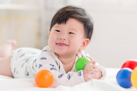 Happy cute adorable Asian baby boy with toys and sweet smiley face. Archivio Fotografico